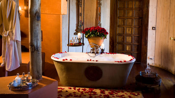 Ngorongoro Crater Lodge - With a centrepiece of red roses has twin hand basins, shower, chandelierlit bathtub and seperate wc